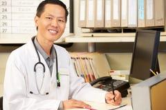 El doctor Working At Nurses Station Fotografía de archivo libre de regalías