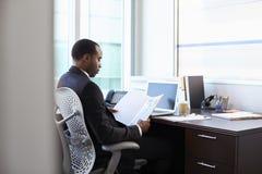 El doctor Working Reading Notes en el escritorio en oficina Imagen de archivo