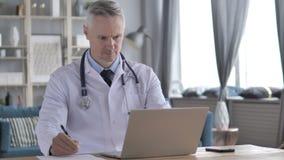 El doctor Writing Medical Report del paciente y del trabajo en el ordenador portátil almacen de video