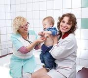 El doctor y la enfermera de sexo femenino examinan al pequeño bebé enojado Fotos de archivo libres de regalías