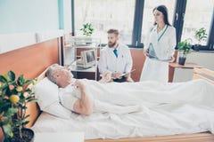 El doctor y la enfermera jovenes están visitando al paciente envejecido en el m brillante Imagen de archivo libre de regalías