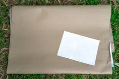 El documento de Flipboard sobre la hierba con tamaño del Libro Blanco a4 en el top, se prepara para el taller del estudiante univ foto de archivo