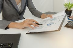 El documento del beneficio del control del hombre de negocios y calcula alrededor y observa los datos costados en la oficina fotos de archivo libres de regalías