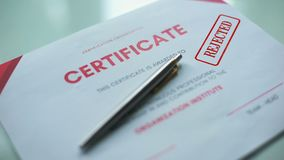 El documento del certificado rechazó, mano que sellaba el sello en el papel oficial, evaluación almacen de metraje de vídeo