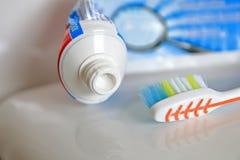 El DOF bajo tiró de un cepillo de dientes y de una crema dental en una superficie brillante Imágenes de archivo libres de regalías