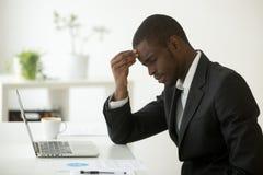 El dolor de cabeza en el concepto del trabajo, hombre de negocios africano subrayado siente el str fotos de archivo