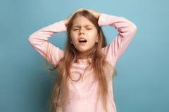 El dolor de cabeza Muchacha adolescente en un fondo azul Expresiones faciales y concepto de las emociones de la gente Foto de archivo libre de regalías