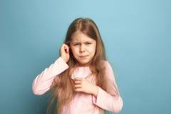 El dolor del oído Muchacha adolescente en un fondo azul Expresiones faciales y concepto de las emociones de la gente Fotografía de archivo libre de regalías
