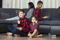 El domicilio familiar hermoso feliz con los ordenadores portátiles y las tabletas se sientan en foto de archivo libre de regalías