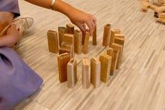 El dominó de madera se alineó por la mano de un hombre fotografía de archivo