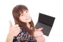 El donante feliz de la muchacha del ordenador portátil manosea con los dedos encima de la muestra del éxito que se sienta en la P Imágenes de archivo libres de regalías