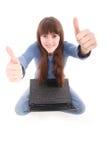 El donante feliz de la muchacha del ordenador portátil manosea con los dedos encima de la muestra del éxito que se sienta en la P Fotografía de archivo
