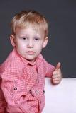 El donante joven del muchacho los pulgares sube gesto Foto de archivo