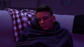 El dormir adolescente delante de la TV en casa, perdiendo la hora para la experiencia recreativa almacen de video