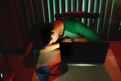 El dormir adolescente joven delante de un ordenador portátil Foto de archivo libre de regalías