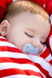 El dormir adorable del bebé envuelto en una manta roja Fotografía de archivo libre de regalías