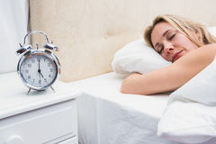 El dormir bastante rubio en cama con el despertador Fotografía de archivo