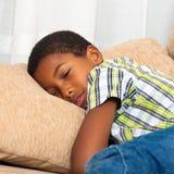 El dormir cansado del muchacho del niño Imagenes de archivo