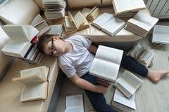 El dormir cansado del muchacho rodeado por los libros en sitio Imagen de archivo libre de regalías