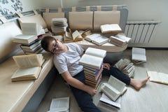El dormir cansado del muchacho rodeado por los libros en sitio Fotos de archivo