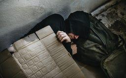 El dormir de la persona sin hogar al aire libre en el camino Fotografía de archivo