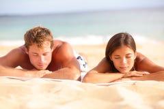 El dormir de relajación de los pares jovenes en la playa Foto de archivo libre de regalías