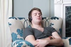 El dormir de relajación en auriculares de la silla Imágenes de archivo libres de regalías