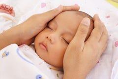 El dormir del bebé y mano del padre Foto de archivo libre de regalías