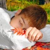 El dormir del muchacho al aire libre Fotografía de archivo libre de regalías