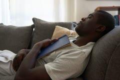 El dormir del sofá del sofá del libro del hombre foto de archivo libre de regalías