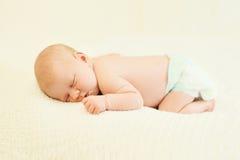 El dormir dulce del bebé en su estómago en hogar de la cama Foto de archivo libre de regalías