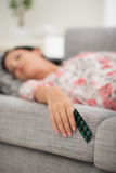 El dormir femenino joven con el paquete de píldoras Imagenes de archivo