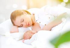 El dormir junto y madre de amamantamiento y bebé recién nacido en b Imagen de archivo libre de regalías