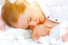 El dormir junto y madre de amamantamiento y bebé recién nacido en b Foto de archivo libre de regalías