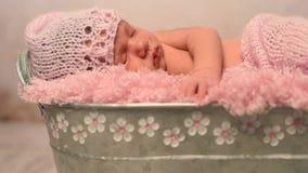 El dormir precioso recién nacido en sombrero y manta rosados en choza almacen de video