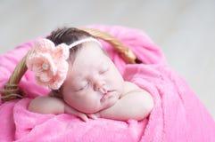 El dormir recién nacido con la flor hecha punto en la cabeza Primer infantil del bebé que miente en la manta rosada en cesta Retr Foto de archivo libre de regalías