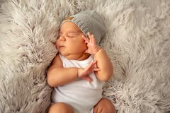 El dormir recién nacido del niño del muchacho en sombrero en la manta mullida imagen de archivo