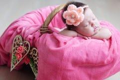 El dormir recién nacido Primer infantil del bebé que miente en la manta rosada en la cesta adornada con el corazón de madera Imagenes de archivo