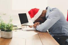 El dormir trabajando demasiado al hombre de negocios negro con el ordenador portátil imagen de archivo libre de regalías