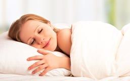 El dormir y sonrisas hermosos de la mujer en el suyo sueño en cama Imagenes de archivo