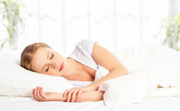 El dormir y sonrisas hermosos de la mujer en el suyo sueño en cama Fotos de archivo