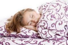 El dormir y sonrisas hermosos de la mujer en el suyo sueño en cama Fotografía de archivo