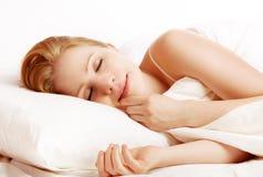 El dormir y sonrisas hermosos de la mujer en el suyo sueño en cama Imagen de archivo