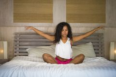 El dormitorio afroamericano negro atractivo y feliz joven de la mujer en casa que hace la meditación de la yoga y el ejercicio de fotos de archivo libres de regalías