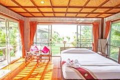 El dormitorio brillante y espacioso, ventana amplia, piso de madera, palmeras cultiva un huerto exterior Estilo tropical de relaj imágenes de archivo libres de regalías