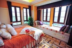 El dormitorio con las ventanas grandes rodeó Fotos de archivo libres de regalías