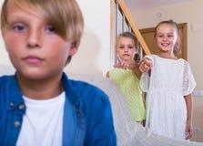 El dos hablar de las muchachas y muchacho malhumorado que se sientan por separado en casa Fotos de archivo libres de regalías