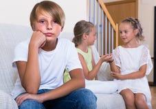 El dos hablar de las muchachas y muchacho malhumorado que se sientan por separado en casa Foto de archivo