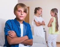 El dos hablar de las muchachas y muchacho malhumorado que se sientan por separado en casa Fotografía de archivo