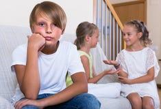 El dos hablar de las muchachas y muchacho malhumorado que se sientan por separado en casa Imagen de archivo libre de regalías